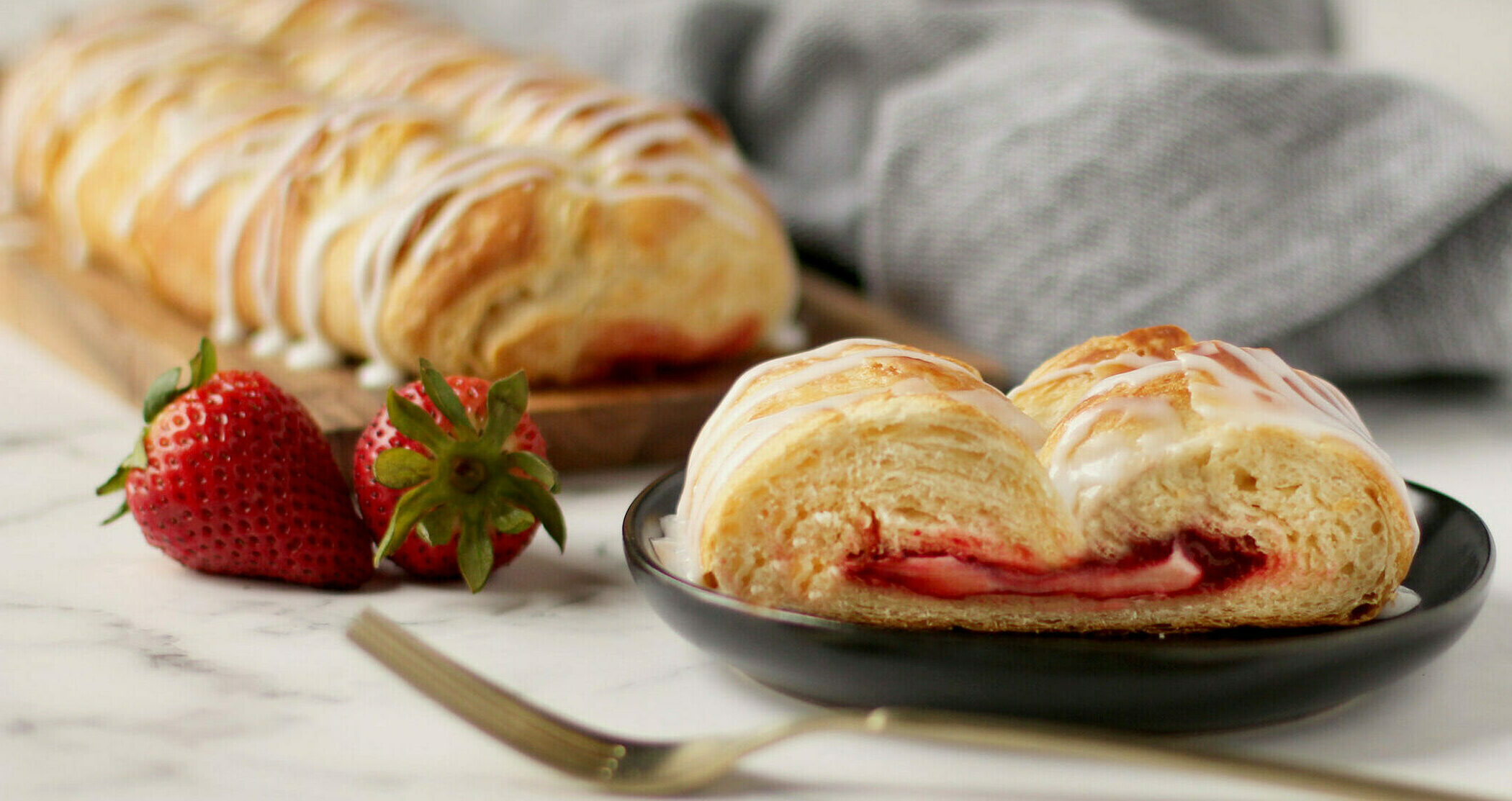 Strawberry Cream Cheese Pastry with icing in the background. A slice of pastry on a plate with fork and strawberries.